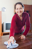 Smiling mature woman in red cleaning  table   — Stock Photo