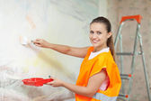 woman in uniform paints wall   — Stock Photo