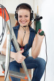Portrait of happy girl in headphones with drill   — Stock Photo