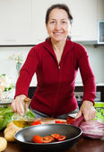 Mature woman pouring oil to frying-pan — Stock Photo