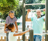 Middle-aged man with family training on chin-up bar   — Stock Photo