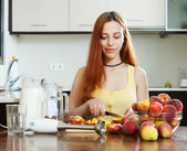 Long-haired girl in yellow  with peaches at home  — Stock Photo