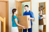 Courier in uniform brought package to housewife — Stock Photo