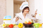 Young woman in toque cooks from vegetables  — Stock Photo