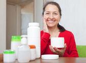 Donna matura felice mette la crema sul viso — Foto Stock