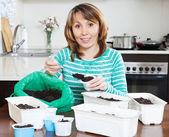 Girl in green making soil for seedlings — Stock Photo