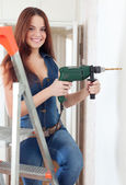 Happy girl drills hole in  wall   — Stock Photo