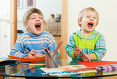 Emotional children playing with paper and pencils  — Stock Photo