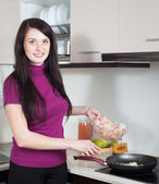 Happy woman cooking prawns in frying pan — Stock Photo
