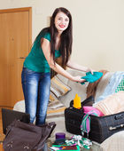 Smiling brunette woman packing suitcase   — Photo