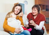 Woman with mature mother caring for sick baby — ストック写真