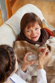Nurse caring for unwell mature woman — Stock Photo