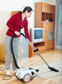 Mature woman cleaning with vacuum cleaner — Stock Photo