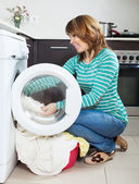 Woman doing laundry with washing machine — Stockfoto