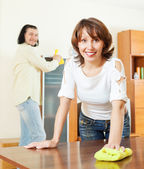 Woman with husband dusting wooden furiture — Stock Photo