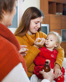 Two women caring for unwell toddler — Stock Photo