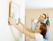 Uomo e donna appesa la foto d'arte in cornice sul muro — Foto Stock
