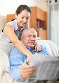 Happy couple of grandparents with newspaper — Stock Photo