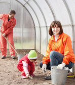 Women with child works at hothouse — Stock Photo
