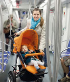 Smiling young mother with baby  at metro — Stock Photo