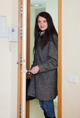 Woman in coat loocking door  — Foto de Stock