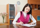 Serious woman filling in financial documents   — Photo