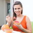 Happy woman eating grapefruit — Stock Photo