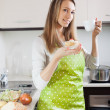 Woman in apron eating cakes with tea — Stock Photo