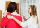 Girl measuring the shoulders of  friend — Stock Photo