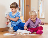 Children  playing with electrical extension — Stock Photo
