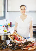 Young smiling housewife with raw seafood — Stock Photo
