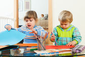 Serious children playing with paper and pencils   — Stock Photo