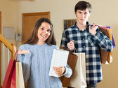 Smiling couple with purchases — Stock Photo