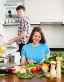 Woman cooking food while man washing dishes — Stock Photo