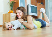 Happy mom with child on wooden floor  — Stock Photo