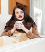 Happy girl with cup near calorifer   — Stock Photo