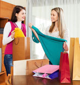 Happy girlfriends  looking purchases — Stock Photo