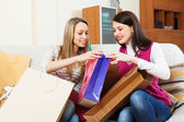 Smiling women together looking purchases   — Stock Photo