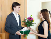 Happy man with flowers and gift box — Stock Photo