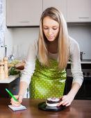 Blonde girl weighing cakes — Stock Photo