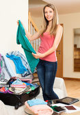 Smiling woman  packing clothes into suitcase — Stock Photo