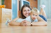 Donna sorridente con un bambino sul pavimento — Foto Stock