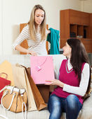 Casual  girls together looking purchases   — Stock Photo