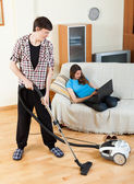 Clean up man, while wife lying with notebook — Stock Photo