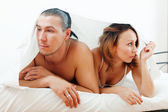 Unhappy couple under sheet — Stock Photo