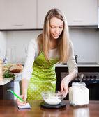 Blonde woman weighing flour — Stock Photo