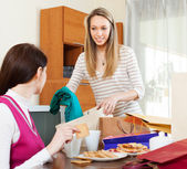 Woman showing purchases  to girlfriend — Stock Photo