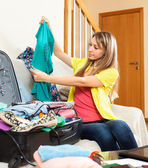 Young woman sitting on a sofa near the open suitcase  — Stock Photo