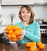 Happy  woman holding  heap of mandarins — Stock Photo