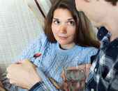 Man giving  sirup to unwell girlfriend   — Stock Photo